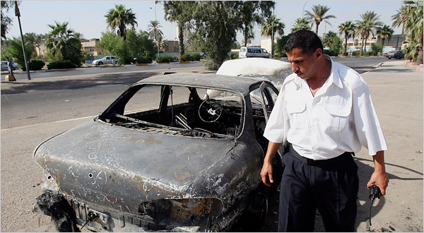 An Iraqi police officer inspecting a car destroyed in the Nisour Square shooting